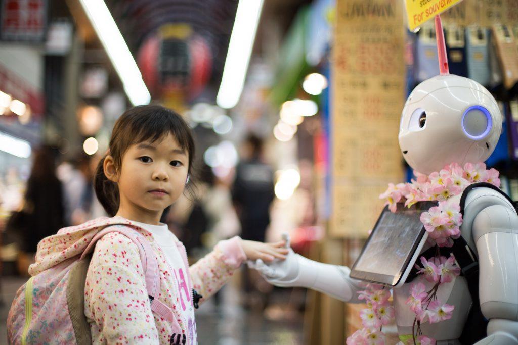 Ein junges Mädchen reicht einem Roboter die Hand